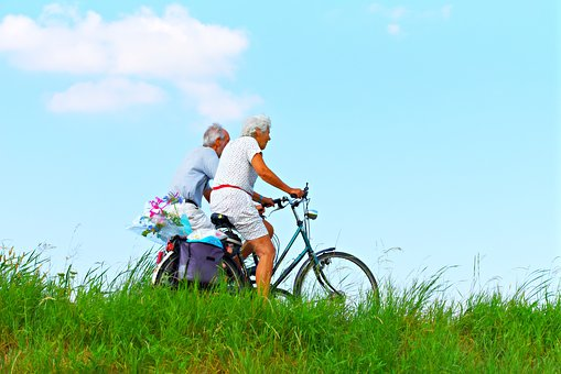 exercise for elderly man and woman cycling bikes